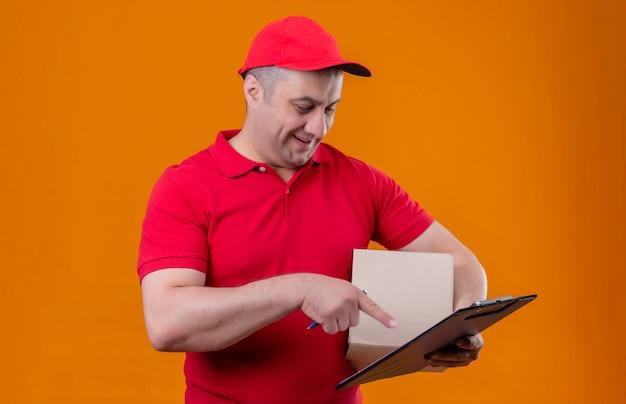 Fattorino che indossa il pacchetto e la lavagna per appunti della scatola della tenuta del cappuccio e dell'uniforme rossa che indicano con il dito indice sorridendo sopra la parete arancio isolata