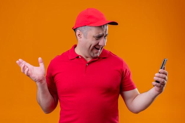 Fattorino che indossa l'uniforme rossa e cappuccio che esaminano schermo del suo smartphone che ritiene deludente sopra la parete arancio isolata