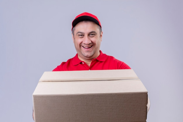 Fattorino che indossa l'uniforme rossa e cappuccio che giudicano sorridere grande della scatola di cartone amichevole con il fronte felice sopra la parete bianca isolata