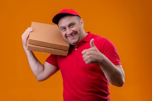 Fattorino che indossa l'uniforme rossa e cappuccio che tengono i contenitori di pizza positivi e felici che mostrano i pollici su sopra la parete arancio