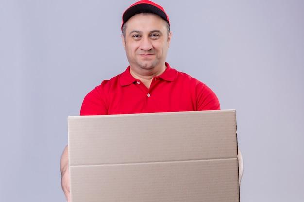 Fattorino che indossa l'uniforme rossa e cappuccio che tiene scatola di cartone che sembra sorridere sicuro sopra la parete bianca isolata