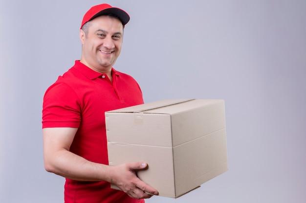 Fattorino che indossa l'uniforme rossa e la scatola di cartone della tenuta del cappuccio che sembrano sicure con il sorriso sul fronte sopra la parete bianca isolata