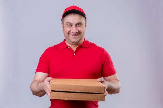 Fattorino che indossa l'uniforme rossa e le scatole della pizza della tenuta del cappuccio che sorridono amichevoli con il fronte felice sopra la parete bianca isolata