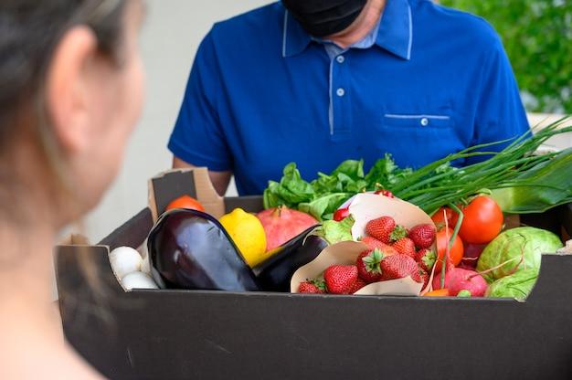 Fattorino che indossa una maschera e che tiene una scatola con le verdure