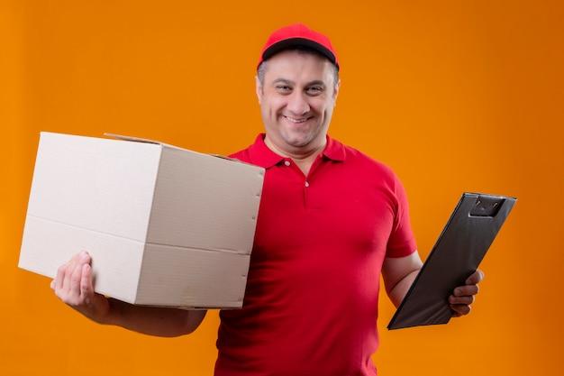 Fattorino che indossa uniforme rossa e cappuccio che tengono sorridere positivo e felice della scatola di cartone e della lavagna per appunti sopra la parete arancio
