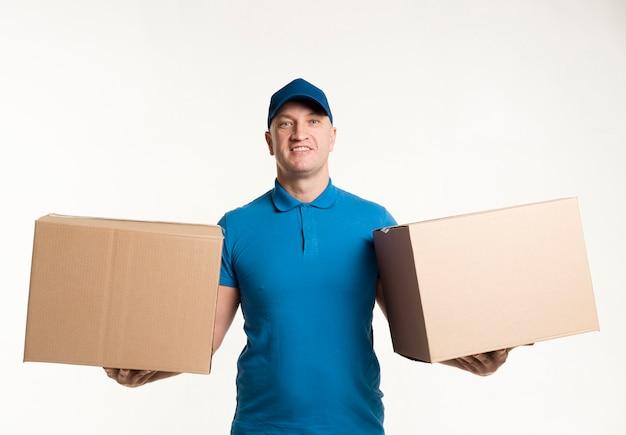 Fattorino che posa con le scatole di cartone in ogni mano