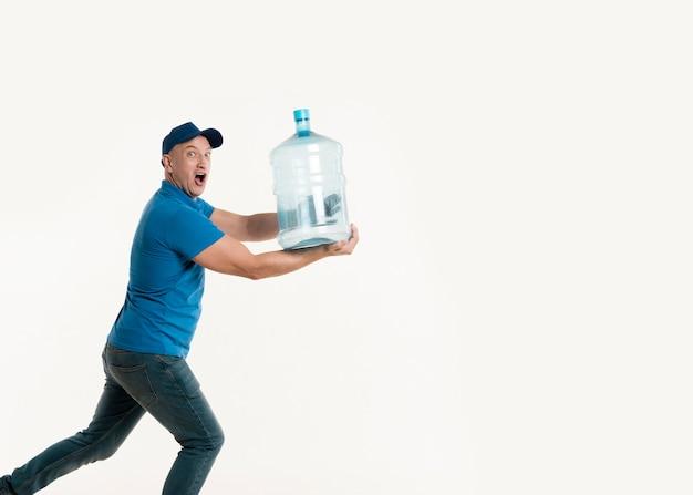 Fattorino che posa mentre tenendo bottiglia di acqua