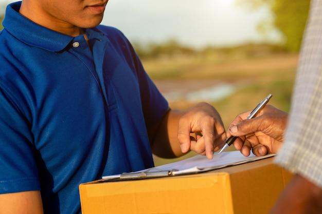 Fattorino che tiene consegna marrone delle scatole di cartone o del pacco al cliente alla campagna