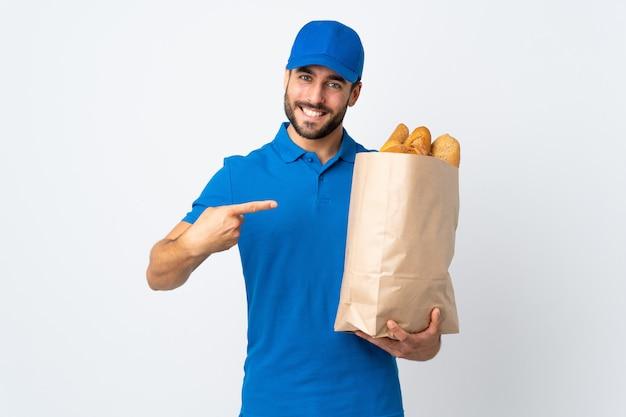 Fattorino che tiene una borsa piena di pani sulla parete bianca e che lo indica