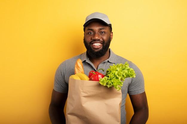 Fattorino con espressione felice pronto a consegnare la borsa con il cibo. sfondo giallo