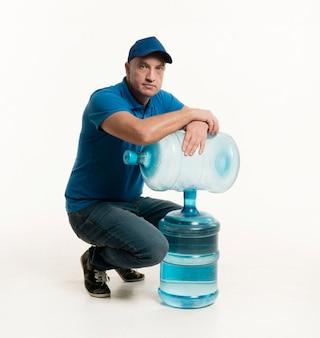 Fattorino con il cappuccio che posa con le bottiglie di acqua