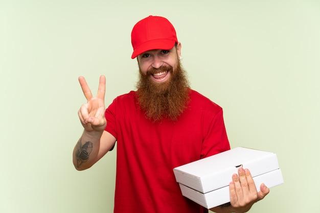 Fattorino con la barba lunga sopra fondo verde isolato che sorride e che mostra il segno di vittoria