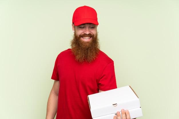 Fattorino con la barba lunga sopra fondo verde isolato con l'espressione felice