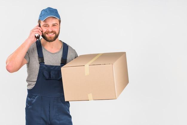 Fattorino con scatola parlando per telefono