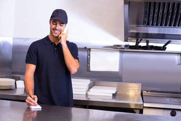 Fattorino della pizza che prende un ordine per telefono
