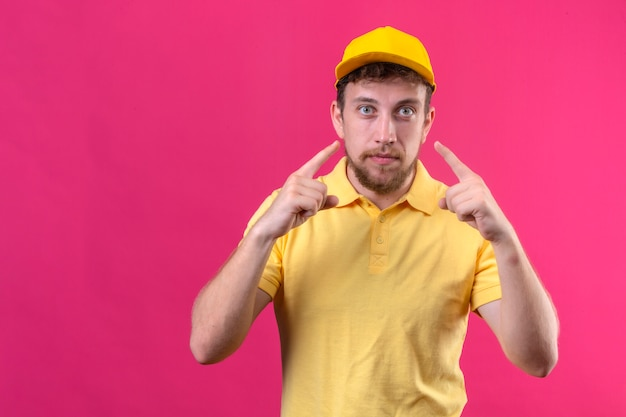 Fattorino in maglietta polo gialla e berretto che punta agli occhi guardandoti gesto in piedi sul rosa