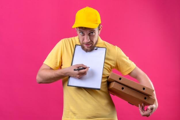 Fattorino in maglietta polo gialla e berretto con scatole per pizza e appunti chiedendo firma in piedi sul rosa
