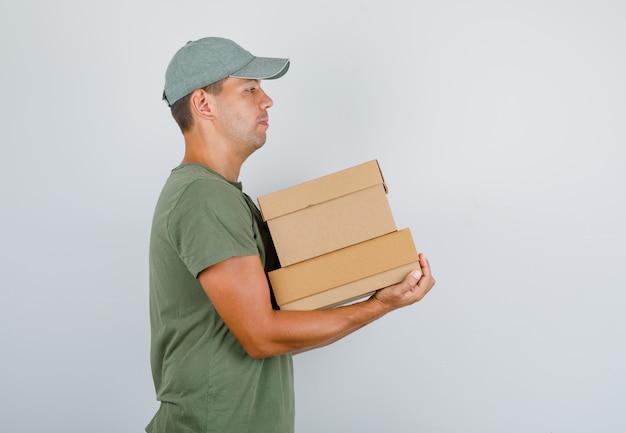 Fattorino in maglietta verde, cappuccio che tiene scatole di cartone e sembra fiducioso.
