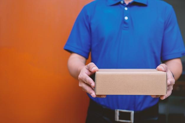 Fattorino in uniforme blu che passa la scatola del pacco al destinatario - concetto di servizio di corriere