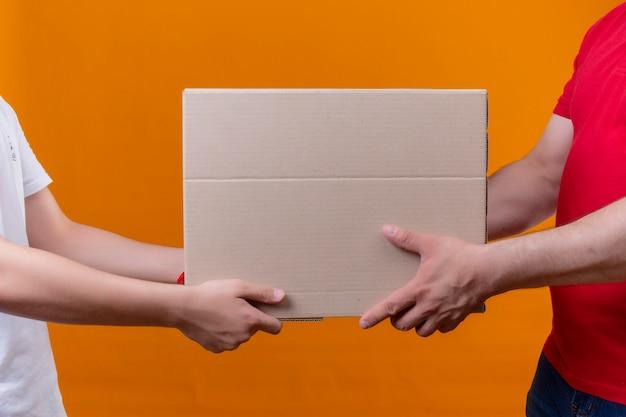 Fattorino in uniforme rossa che dà il pacchetto della scatola ad un cliente sopra la parete arancio isolata