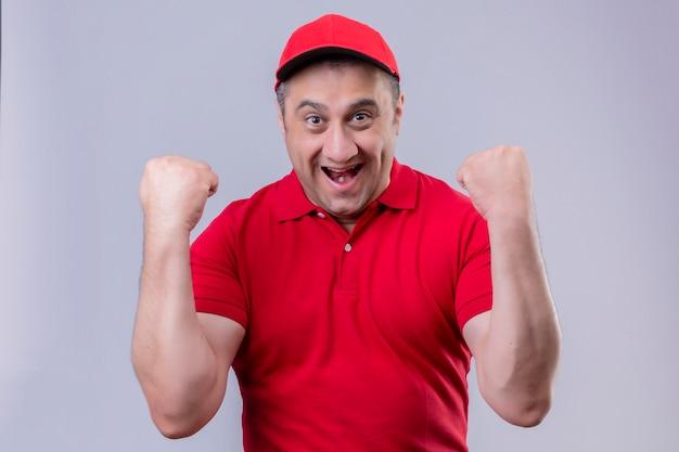 Fattorino in uniforme rossa e cappello guardando uscito rallegrandosi del suo successo e della vittoria stringendo i pugni con gioia felice di raggiungere il suo scopo e gli obiettivi in piedi sul bac blu isolato