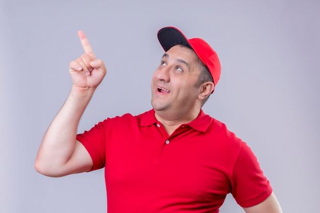 Fattorino in uniforme rossa e cappello sorridente alzando lo sguardo e indicando con il dito qualcosa in piedi sul bianco