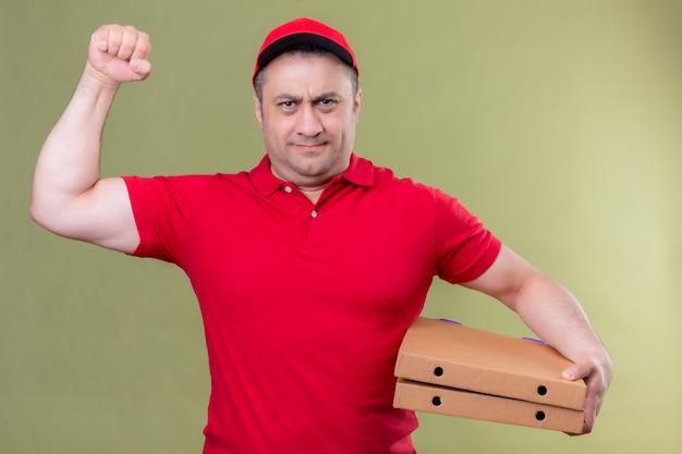 Fattorino in uniforme rossa e cappuccio che tiene le scatole della pizza che mostrano il bicipite sulla sua mano, sorridente fiducioso, concetto vincitore in piedi sul verde
