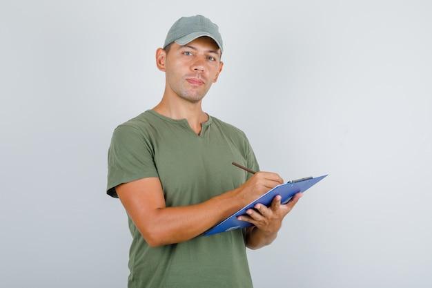 Fattorino prendendo nota negli appunti in t-shirt verde militare, berretto, vista frontale.