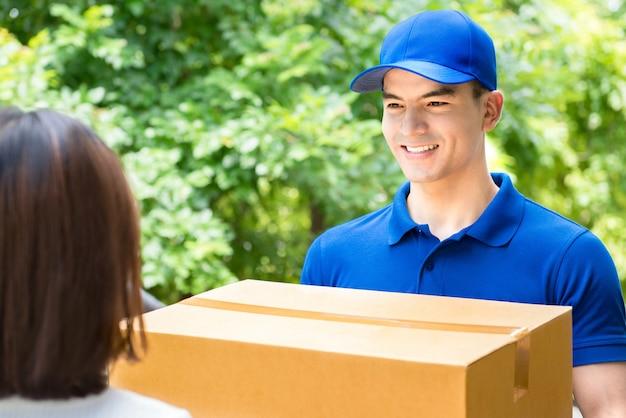 Fattorino sorridente in uniforme blu che consegna il contenitore di pacchi ad una donna