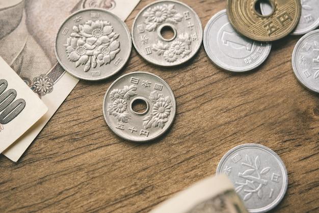 Fatture e monete di soldi di yen giapponesi sulla tavola di legno