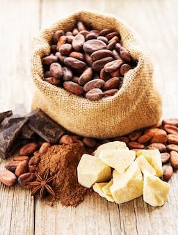 Fave di cacao naturali, polvere, cioccolato e burro su un vecchio fondo di legno