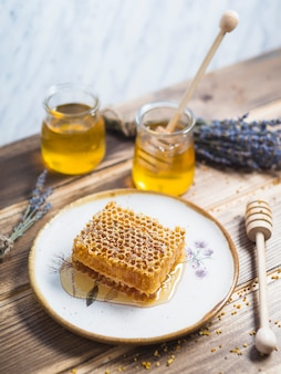 Favo a nido d'ape sul piatto bianco con vaso di miele e lavanda sul tavolo di legno