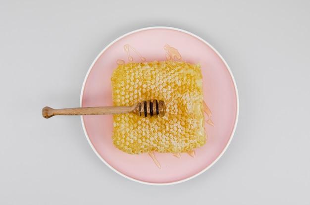 Favo con mestolo sul piatto rosa