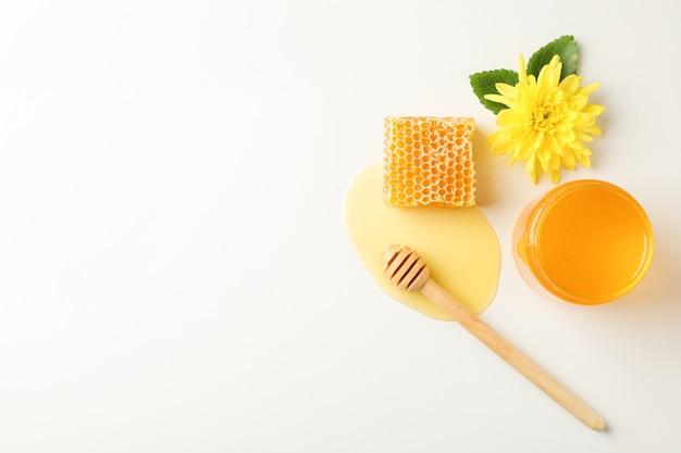 Favo, mestolo, vaso con miele e fiori su sfondo bianco