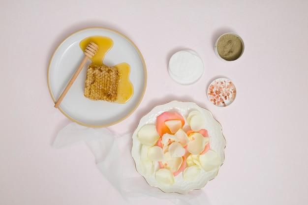 Favo; petali; batuffolo di cotone; argilla rhassoul; salgemma e terreno a base di erbe su sfondo bianco