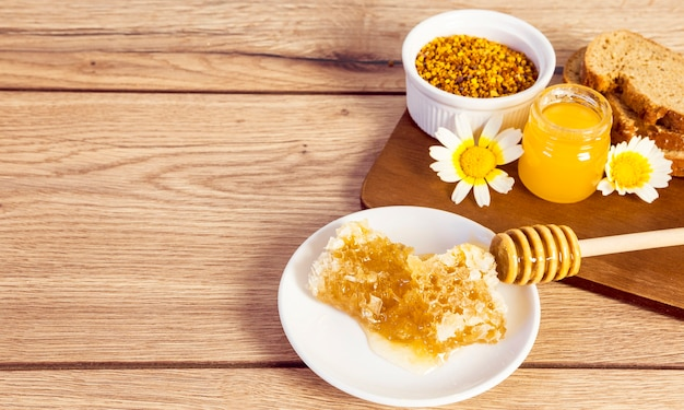 Favo; polline d'api; fetta di pane e miele sulla superficie in legno