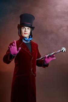 Favoloso uomo del circo con un cappello e un abito rosso in posa nel fumo