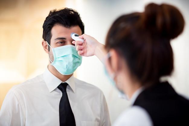 Febbre di controllo da parte dell'operatore digitale thermomiter presso il banco informazioni per scansione e protezione da coronavirus (covid-19)