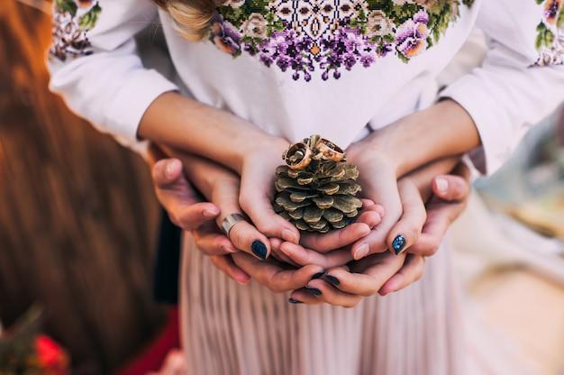 Fede nuziale con le pigne nelle mani della sposa e dello sposo