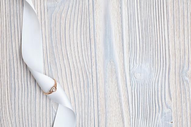 Fede nuziale con un nastro bianco su un fondo di legno. vista dall'alto.