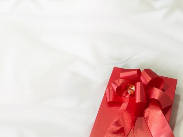 Fede nuziale del diamante sul nastro rosso del contenitore di regalo