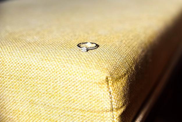 Fede nuziale in argento con diamante incastonato, isolata su tessuto vintage.
