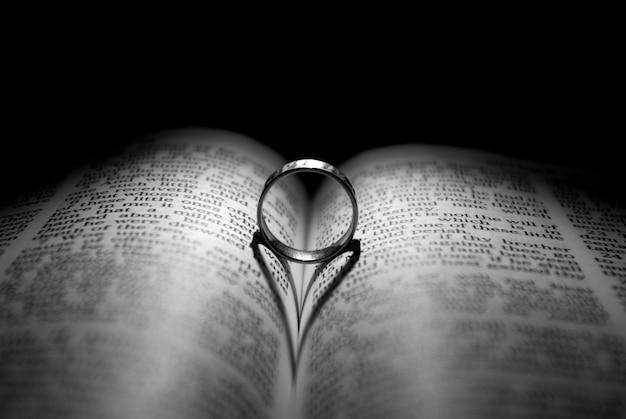 Fede nuziale sul libro, la sua ombra ha la forma di un cuore