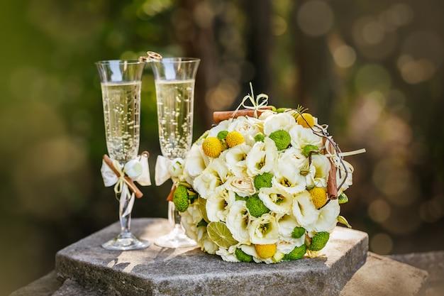 Fedi nuziali con rose e bicchieri di champagne