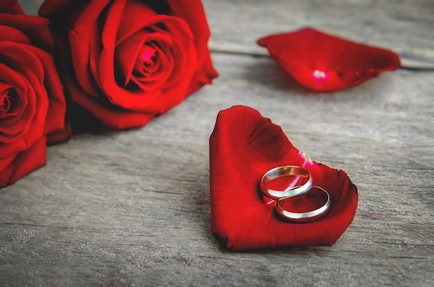 Fedi nuziali delle coppie sul petalo della rosa rossa con il mazzo del fiore della rosa rossa su fondo di legno