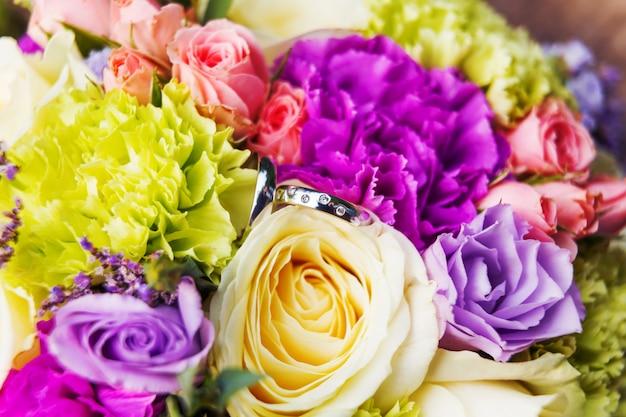 Fedi nuziali dorate con diamanti sul bouquet da sposa
