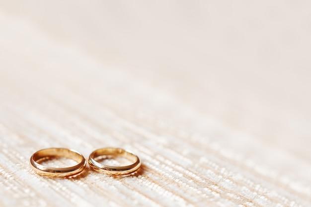 Fedi nuziali dorate su beige. dettagli di nozze, simbolo di amore e matrimonio.
