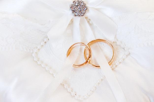 Fedi nuziali dorate su seta bianca