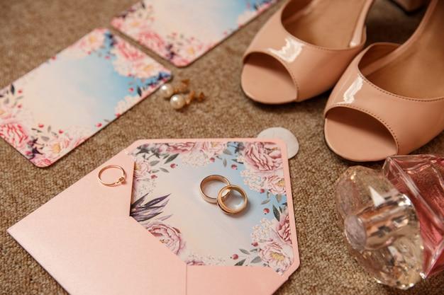 Fedi nuziali e anello di fidanzamento su invito di nozze vicino a scarpe da sposa su tacchi alti. accessori per la sposa