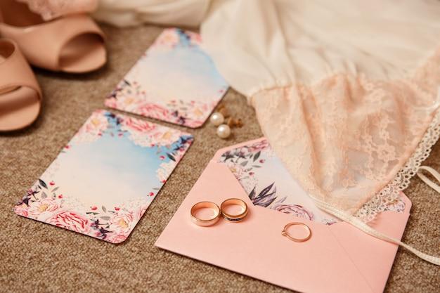 Fedi nuziali e anello di fidanzamento sull'invito di nozze vicino alla biancheria intima e alle scarpe nuziali sui tacchi alti. accessori per la sposa